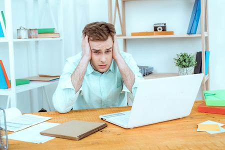 coder: IT company. Young programmer working with laptop. Nice office interier. Professional coder is tired Stock Photo