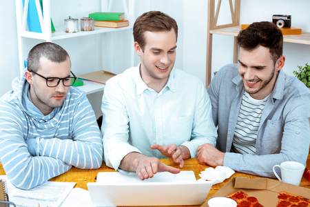 IT company. Young programmers working with laptop with pizza. Nice office interier. Professional coders looking at laptop and smiling Stockfoto