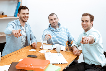 IT company. Young programmers working with laptop. Nice office interier. Professional coders looking and pointing at camera, and smiling Stock Photo
