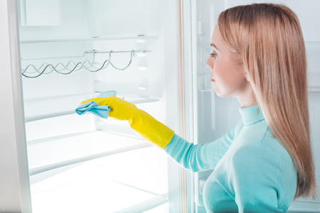 Pretty blonde washing big white fridge. Young woman with gloves