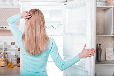 Ce qui est pour le dîner? debout Jolie blonde ouverte près de frigo vide. Vue arrière photo de jeune femme réfléchie. Elle regarde réfrigérateur