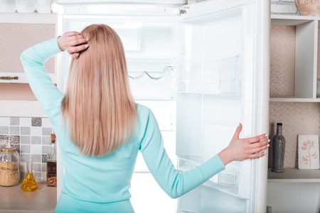 freezer: Whats for dinner? Pretty blonde standing near open empty fridge. Back view photo of thoughtful young woman. She looking at fridge Stock Photo