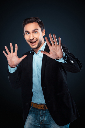 Studio shot of caucasian young businessman. Businessman smiling and surprisingly looking at camera Фото со стока