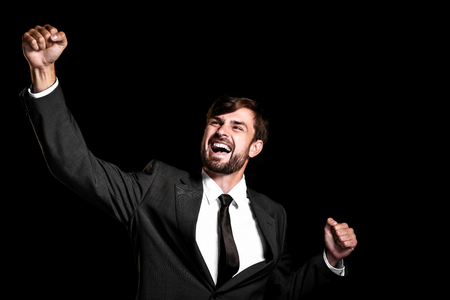 Stylish young businessman on black background. Businessman cheerfully rejoicing Banco de Imagens