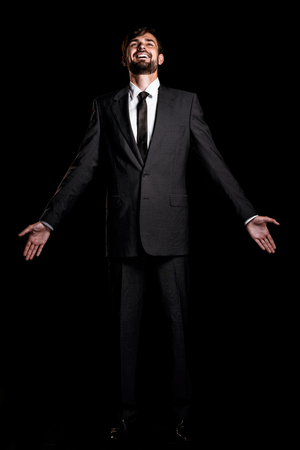 Stylish young businessman on black background. Businessman cheerfully looking up