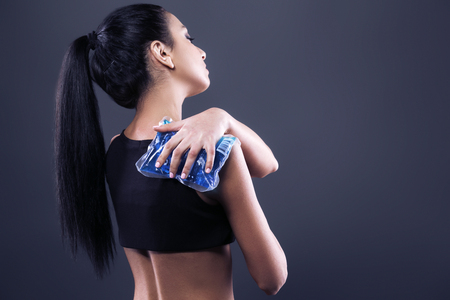 dark brown hair: Body pain. Studio shot of beautiful young woman with dark brown hair. Woman suffering from shoulder pain. Woman holding freezing gel on shoulder