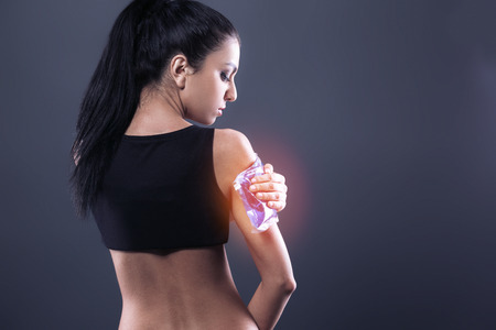 dark brown hair: Body pain. Studio shot of beautiful young woman with dark brown hair. Woman suffering from arm pain. Red spot on arm. Woman holding freezing gel on arm