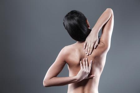dark brown hair: Body pain. Studio shot of beautiful young woman with dark brown hair. Woman suffering from backache