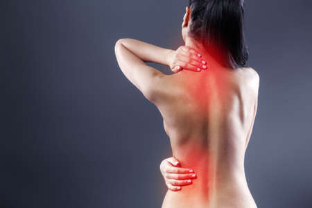 dark brown hair: Body pain. Studio shot of beautiful young woman with dark brown hair. Woman suffering from backache. Red spot on back Stock Photo