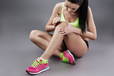 dark brown hair: Body pain. Studio shot of beautiful young sporty woman with dark brown hair. Woman suffering from knee pain Stock Photo