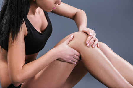 dark brown hair: Body pain. Studio shot of beautiful young woman with dark brown hair. Woman suffering from knee pain