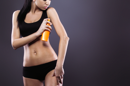 dark brown hair: Body care. Studio shot of beautiful young woman with dark brown hair. Woman using tanning product