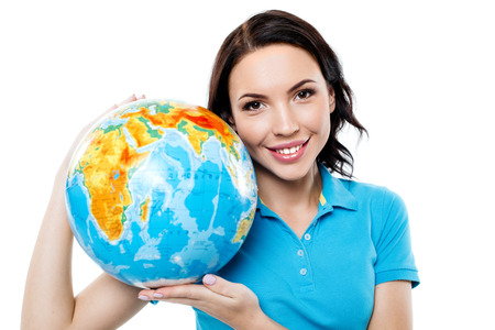 business globe: Travel concept. Portrait of stylish beautiful young woman isolated on white background. Woman smiling, looking at camera and holding globe Stock Photo