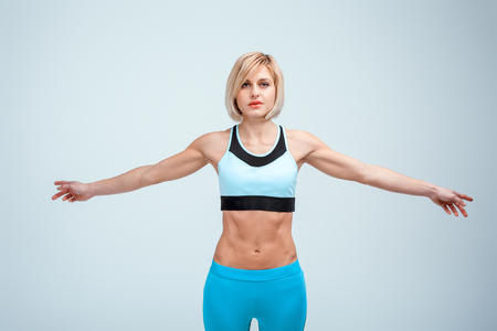 Portrait of beautiful caucasian blonde sporty woman. Young athlete holding arms to sides and looking at camera