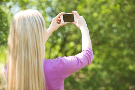 nice looking: Nice looking young woman outdoors. Woman making selfie photo with mobile phone. Beautiful green park as a background