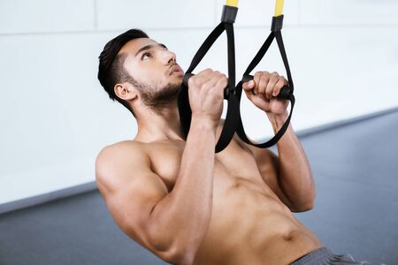 Young man training with TRX