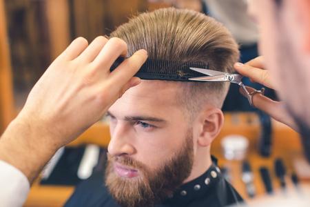 Giovane uomo nel negozio di barbiere Concetto di cura dei capelli Archivio Fotografico - 76673762