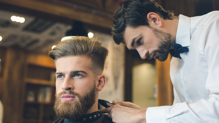 Jonge Mens in Barbershop Hair Care Service Concept Stockfoto
