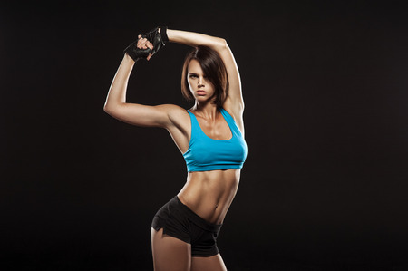 Young woman athlet muscle body portrait in gym