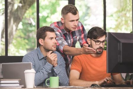 Jonge mannen programmeurs samenwerken in het kantoor