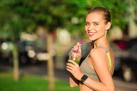 若い女性屋外スムージー健康的なデトックスで飲む 写真素材