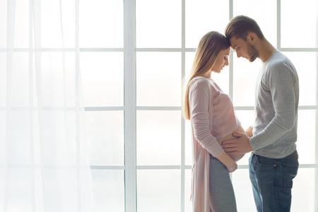 若いカップル期待して赤ちゃんが室内で一緒に立って