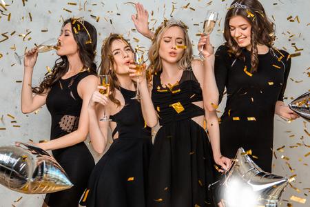 Jonge vrouwen die samen kippenpartij vieren die op wit wordt geïsoleerd