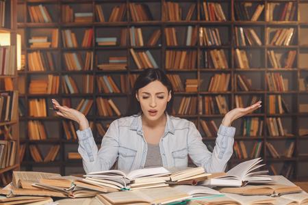 Jonge vrouw studeert alleen in de bibliotheek