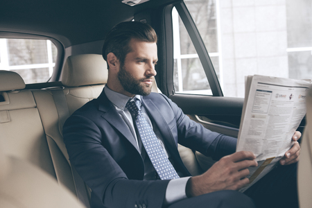 Young business person test drive new vehicle reading newspaper
