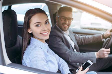 スマート フォンを保持しているモダンなエコ車で男と女の交通 写真素材