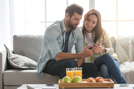 Young woman and man family couple indoors using smartphone Stock Photo