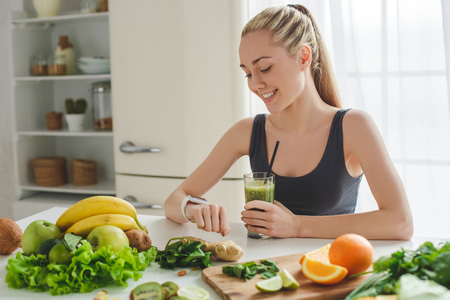 Young woman making detox smoothie at home