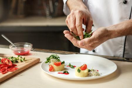 Oudere man professionele chef-kok koken maaltijd binnenshuis Stockfoto