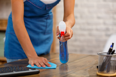 Close up studio shot of housekeeper. Beautiful woman cleaning table with spray. Focus on hands