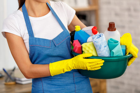 Studio shot of housekeeper while cleaning office. Woman wearing gloves and holding bowl full of bottles with disinfectant Zdjęcie Seryjne