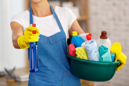 Studio shot of housekeeper while cleaning office. Woman wearing gloves and holding bowl full of bottles with disinfectant Stock Photo