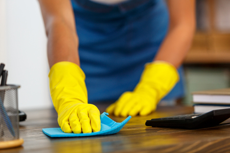 Close up studio shot of housekeeper. Beautiful woman cleaning table. Woman wearing gloves. Focus on hands