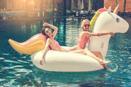 Young women friends in the swimming pool fun