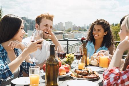 Gruppo di amici che hanno festa di barbecue sul tetto