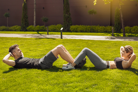 laying abs exercise: Young couple exercise together outdoors healthy lifestyle