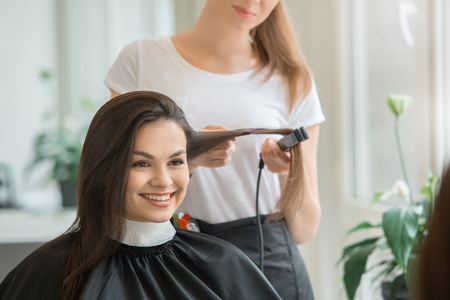 Young female sitting in hair salon hairdo styling straighten with ploy