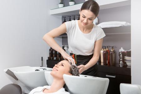 Young female sitting in hair salon hairdo styling washing hair