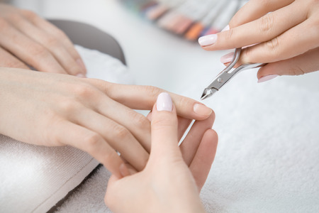 Young female in beauty salon nail care nippers