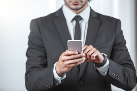 Male person working in the office business holding smartphone