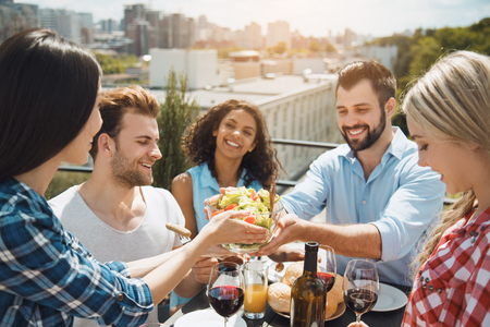 Gruppo di amici che hanno festa di barbecue sul tetto Archivio Fotografico - 84676661