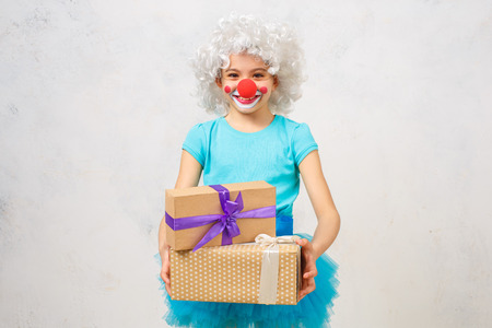 Little girl wearing clown costume isolated on white