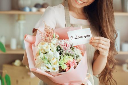 Floristenbesetzung der jungen Frau, die mit Blumen arbeitet