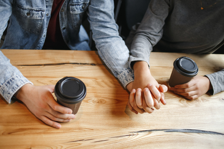 Young boyfriend and girlfriend diverse couple students having a romantic coffee-break drinking hot coffee holding hands closeness concept close-up