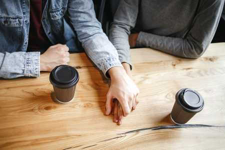 Young boyfriend and girlfriend diverse couple students having a romantic coffee-break holding hands drinking hot coffee romance close-up top view