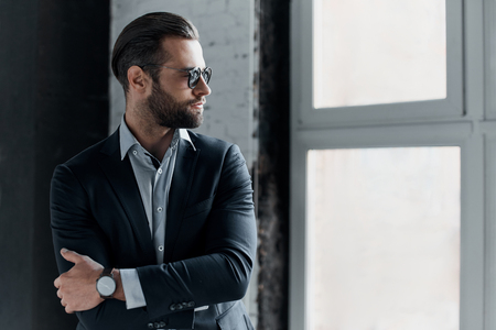 Young bearded stylish businessman leader indoors at office wearing sunglasses walking fixing sleeves with watch looking aside serious Stock Photo